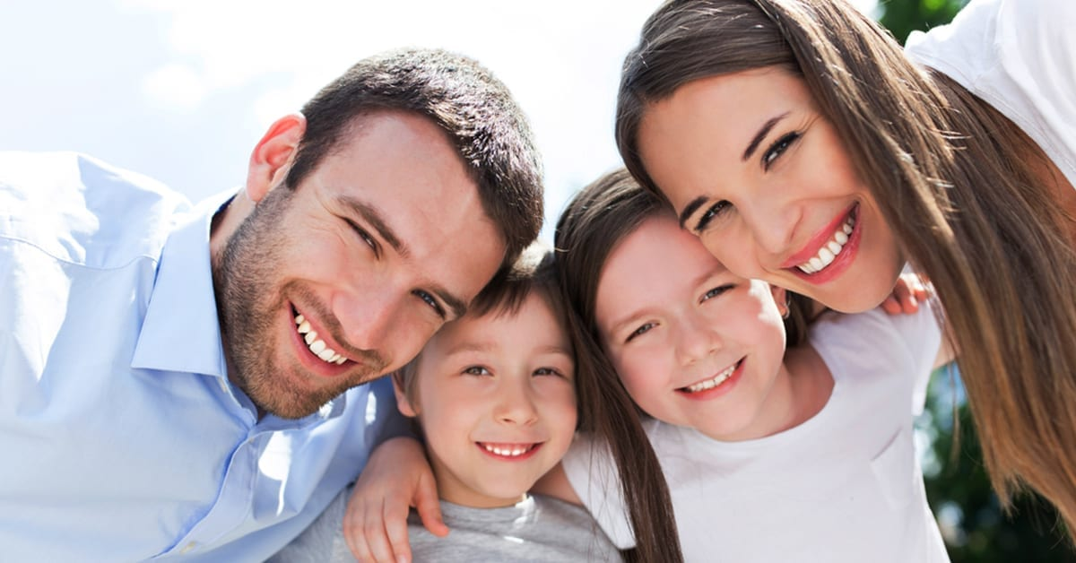 family smiling in front of the camera